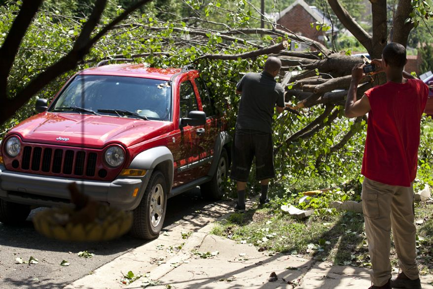Isaac Boone (right) takes photos of the damage to his friend's Jeep as a neighbor steps in to help move the fallen tree in Alexandria on Sunday, Aug. 28, 2011. Winds and rain from Hurricane Irene caused the tree to split. (Andrew S. Geraci/The Washington Times)
