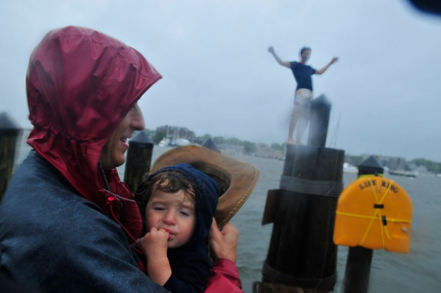 Ben Farrell holds his daughter Nico Farrell, 18 months along City Dock as bands of high winds and heavy rain from Hurricane Irene lash Annapolis, Md., Saturday, August 27, 2011. In background, Jordan Crabtree, of Annapolis, Md., climbs a pier mooring on City Dock. (J.M. Eddins, Jr./The Washington Times)