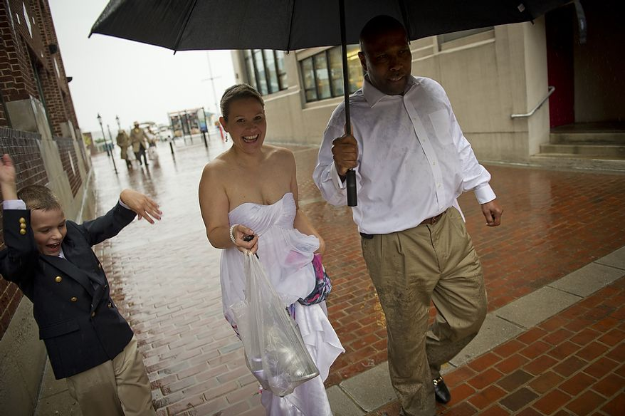 As Hurricane Irene makes her way up the Atlantic coast, newlyweds Sharon and Paul Branner, of Fairfax, Va., are joined by their ringer bearer Vaughn Messner , 9, (left) and flower girl Ryan Messner, 12, (right) as they are caught in the heavy downpour while leaving their wedding reception at the Charthouse at the waterfront in Alexandria, Va, Saturday, August 27, 2011. (Rod Lamkey Jr./The Washington Times)