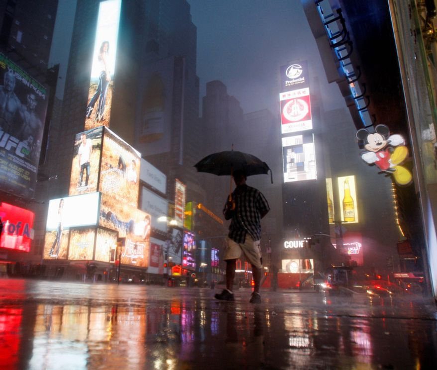 A man walks in Times Square as Tropical Storm Irene arrives in New York, on Sunday, Aug. 28, 2011. (AP Photo/Mike Groll)