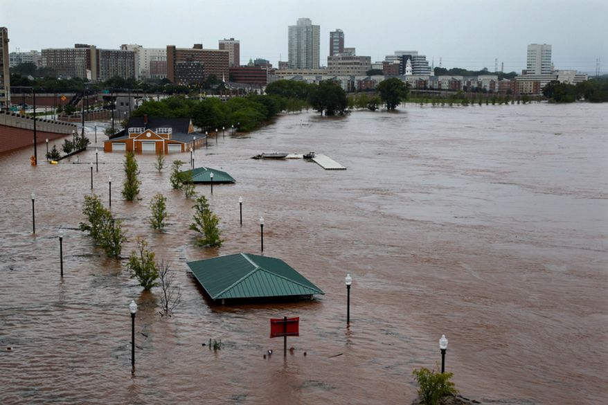 Downtown New Brunswick, N.J., can be see near the overflowing Raritan River Sunday, Aug. 28, 2011, as heavy rains left by Hurricane Irene are causing inland flooding of rivers and streams. (AP Photo/Mel Evans)