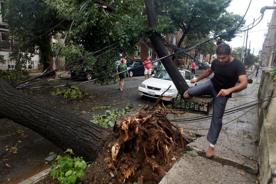 A passerby steps over lines taken down by a large tree, which was blown down by Tropical Storm Irene as it passed through the Astoria neighborhood of the Queens borough of New York, Sunday, Aug. 28, 2011.  (AP Photo/Jason DeCrow)
