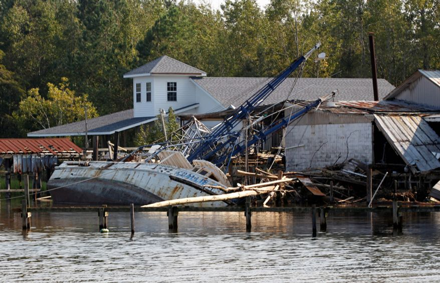 A shrimp boat is bashed against the dock of Daniel's Seafood at the shoreline of the Pamilco River near Aurora, N.C., Sunday, Aug. 28, 2011 after Hurricane Irene hit the North Carolina coast. (AP Photo/Chuck Burton)