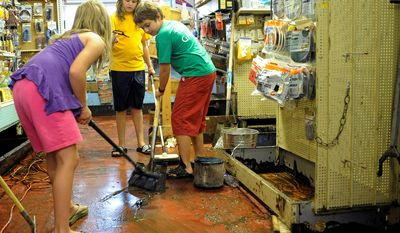 Holly March , left, Abby March, center, and Will Uffelmann, right, all of Keene Valley help family and friends, clean up the mud damage to McDonough'd Valley Hardware Co. caused by Tropical Storm Irene in Keene Valley, N.Y., Monday, Aug. 29, 2011. (AP Photo/Hans Pennink)