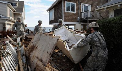 Members of the 192nd Engineer Battalion of Army National Guard from Stratford, Conn., clear debris from beach front property in the aftermath of Tropical Storm Irene in East Haven, Conn., Monday, Aug. 29, 2011.  (AP Photo/Jessica Hill)