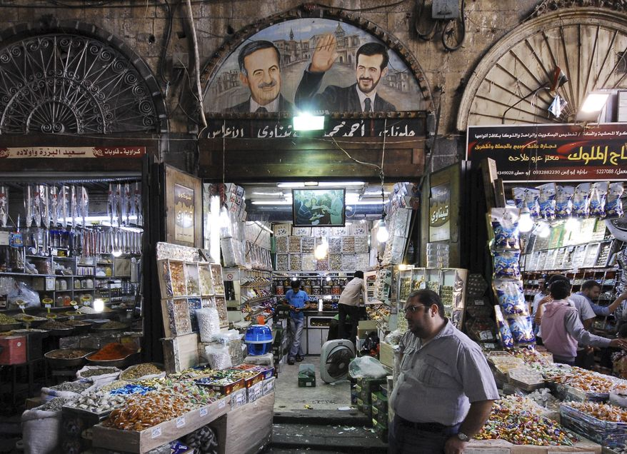 A Syrian sweet vendor stands outside his shop at a popular market in the old city of Damascus, Syria, on Aug. 29, 2011. A picture above the shop depicts the late Syrian President Hafez Assad (left) and his dead son Bassel Assad. (Associated Press)