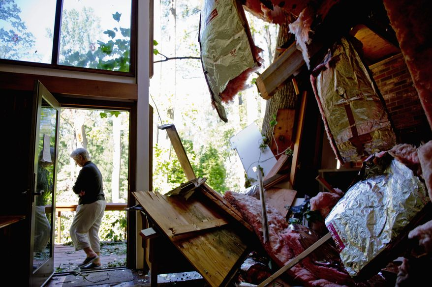 Mary Brogi walks away from her damaged home in Port Republic, Md., after a tree crashed through the roof during Hurricane Irene. (Andrew Harnik/The Washington Times)