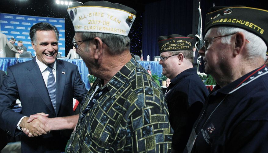 Republican presidential candidate Mitt Romney (left) greets veterans after addressing the Veterans of Foreign Wars in San Antonio on Tuesday. During his speech, Mr. Romney bashed the Obama administration's efforts to cut defense spending. (Associated Press)
