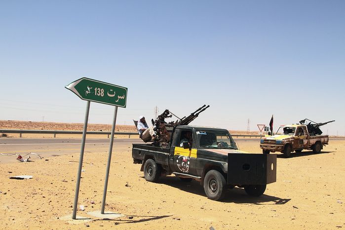 """Libyan rebel vehicles with mounted missile launchers park next to a road sign that reads, in Arabic, """"Sirte,"""" on the front line, 86 miles from Sirte, Libya, on Monday, Aug. 29, 2011. Rebels have been converging from the east and west on Sirte, 250 miles east of Tripoli, preparing to battle forces loyal to Col. Moammar Gadhafi, whose tribe is based in the city. (AP Photo/Gaia Anderson)"""