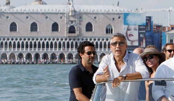 """The Ides of March"" director, writer and actor George Clooney (second from left) arrives in Venice on Tuesday with co-writer Grant Heslov (left). The political drama, which also stars Ryan Gosling, Paul Giamatti, Philip Seymour Hoffman and Marisa Tomei, opened the Venice Film Festival on Wednesday. (Associated Press)"