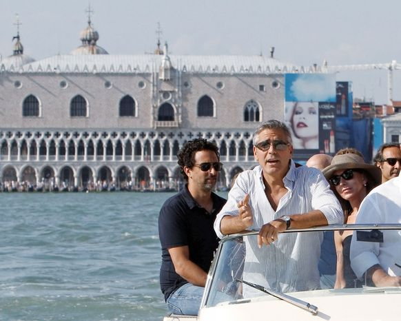 """""""The Ides of March"""" director, writer and actor George Clooney (second from left) arrives in Venice on Tuesday with co-writer Grant Heslov (left). The political drama, which also stars Ryan Gosling, Paul Giamatti, Philip Seymour Hoffman and Marisa Tomei, opened the Venice Film Festival on Wednesday. (Associated Press)"""