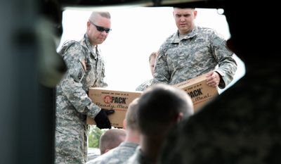 ASSOCIATED PRESS Vermont National Guardsmen load ready-to-eat meals and water for residents of Fair Haven on Wednesday. Vermont Emergency Management officials said all but one of the state's communities left isolated by flooding had been reached by ground crews as of Wednesday.