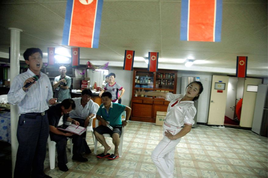 For on-board entertainment, a North Korean man sings karaoke and a waitress dances in a room festooned with North Korean flags. (Associated Press)