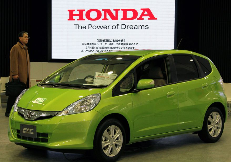 In this Jan. 31, 2010 photo, a visitor inspects a Honda Motor Co.'s hybrid Fit at the Japanese automaker's headquarters in Tokyo. The Fit subcompact beat Toyota Motor Corp.'s Prius hybrid last month to top Japan's auto sales model rankings, its first return to that spot in nearly two years, the Japan Automobile Dealers Association said Friday, Feb. 4, 2011. (AP Photo/Koji Sasahara)