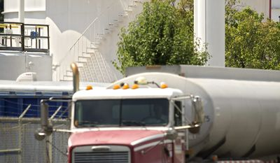 ROD A. LAMKEY/THE WASHINGTON TIMES A tanker truck rolls by a storage tank at the Transmontaigne facility at the Pickett Road tank farm in Fairfax. Federal and state agencies fined Transmontaigne about $114,000 after two spills in 2010.