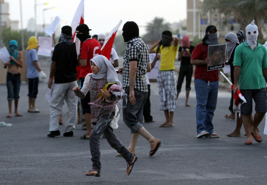A Bahraini girl crosses the street in the midst of masked anti-government protesters in Sitra, Bahrain, on Aug. 31, 2011, hours after the death of 14-year-old Sitra protester Ali Jawad Ahmad. Bahraini security forces clashed with anti-government protesters after Wednesday morning prayers, and the teenager died after being hit by a police tear gas canisters, human rights activists said. (Associated Press)