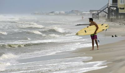 A surfer waits with his board to surf on Sept. 1, 2011, in Dauphin Island, Ala. (Associated Press/Mobile Press-Register)