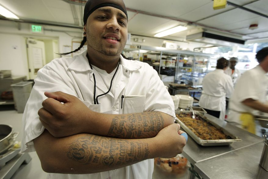 Brandon Hicks show off his tattoo of the Serenity Prayer on his arms as he works at FareStart, The program is offering him a chance to start over.