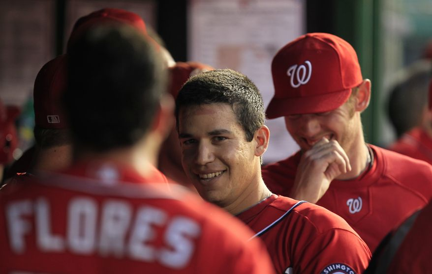 Washington Nationals starting pitcher Tom Milone (center) smiles in the dugout after hitting a three-run homer during the second inning of a baseball game against the New York Mets on Saturday, Sept. 3, 2011, in Washington. (AP Photo/Luis M. Alvarez)