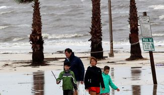 Chris and Kristen Hogan of Biloxi, Miss., take a Sunday walk on the beach in Pass Christian, Miss., with their children Sophie and Myers after rains from Tropical Storm Lee forced them from their home when the Biloxi River flooded. (Associated Press)