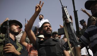 Rebel reinforcements from the Libyan capital of Tripoli celebrate as they arrive at a checkpoint between Tarhouna and Bani Walid, Libya, on Monday, Sept. 5, 2011. (AP Photo/Alexandre Meneghini)