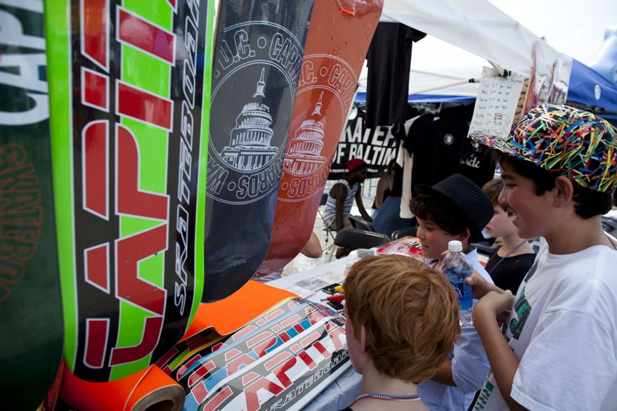 Jake Rowley (right) and his friends check out a booth with skateboards. (Pratik Shah/The Washington Times)