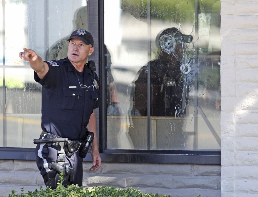 ASSOCIATED PRESS With bullet holes seen in a window, officers look for evidence at the scene of a shooting at an IHOP restaurant in Carson City, Nev., on Tuesday. The gunman killed Two National Guard members, another person and himself.