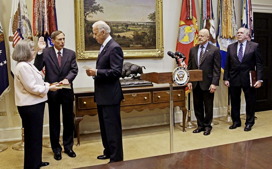 NEW ROLE: David H. Petraeus takes the oath of office Tuesday as director of the CIA with a Bible held by his wife, Holly Knowlton Petraeus. Vice President Joseph R. Biden administered the oath. (Associated Press)