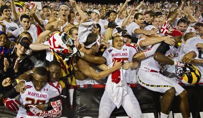 Left to right: Defensive backs Austin Walker (29), Dexter McDougle (25) and wide receiver Quintin McCree, (17) of the Maryland Terrapins celebrate with fans in the student section after their win over the Miami Hurricanes at Byrd Stadium in College Park, on Monday, September 5, 2011. (Andrew Harnik/The Washington Times)