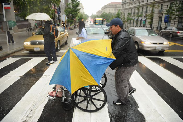 Teresa Milanich, visiting from Argentina, is engulfed by an umbrella as her son, Franco Molina, guides her in a crosswalk at 14th and F streets Northwest during one of several downpours Tuesday afternoon. (Andrew Harnik/The Washington Times)