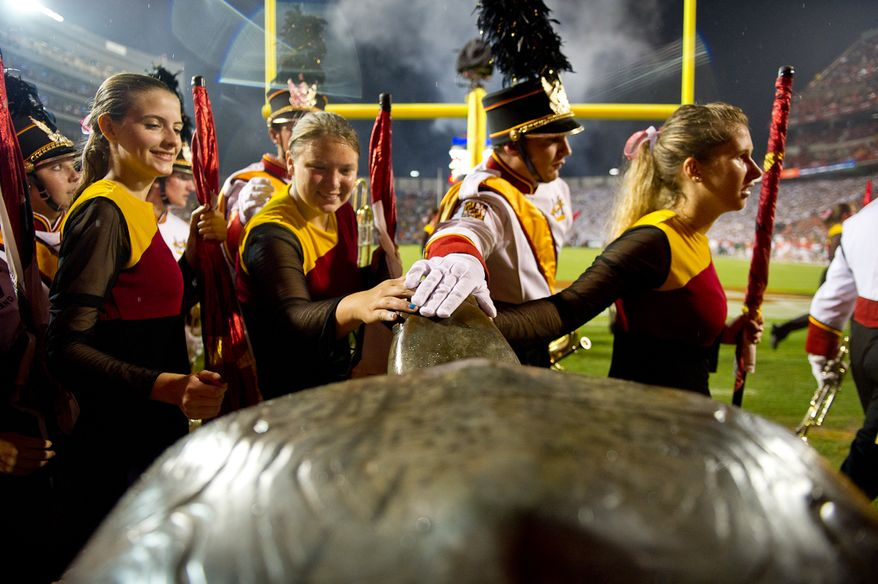 Members of the University of Maryland marching band rub the head of a bronze Terrapin, the school's mascot, before the season opening game against the University of Miami at Byrd Stadium in College Park, MD, Monday September 5, 2011. (Andrew Harnik / The Washington Times)