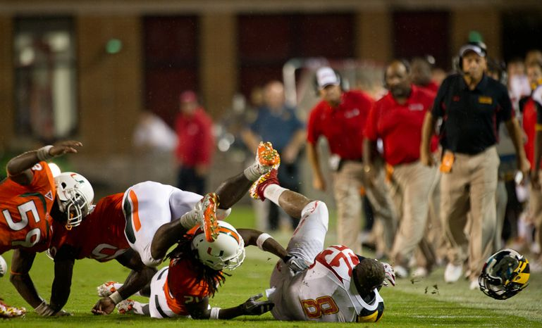 Running back Davin Megget (8) of the Maryland Terps loses his helmet while being tackled by linebackers James Gaines (59), Ramon Buchanan (45), and defensive back Thomas Finnie (20) of the Miami Hurricanes in college football at Byrd Stadium at the University of Maryland in College Park, MD, Monday September 5, 2011. (Andrew Harnik / The Washington Times)