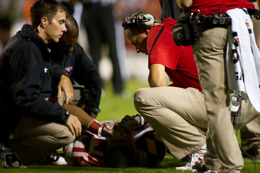 Head coach Randy Edsall, right, comes onto the field to check on injured linebacker Darin Drakeford of the Maryland Terps during the second half at Byrd Stadium at the University of Maryland in College Park, MD, Monday September 5, 2011. (Andrew Harnik / The Washington Times)