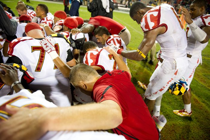 Head coach Randy Edsall of the Maryland Terps pray with his team at  center field after their 32-24 win over the Miami Hurricanes at Byrd Stadium at the University of Maryland in College Park, MD, Monday September 5, 2011. (Andrew Harnik / The Washington Times)