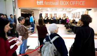 Movie fans wait in line at the box office to purchase Toronto International Film Festival ticket sales on Wednesday. The festival starts Thursday and runs through Sept. 18. Music and documentaries are getting the red carpet treatment this year. (Associated Press)