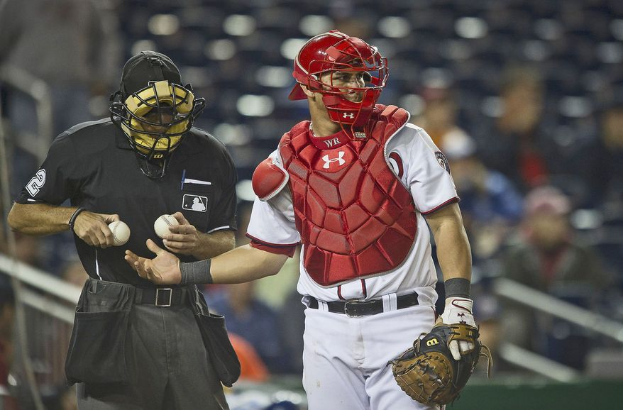 Washington Nationals catcher Wilson Ramos gets a fresh baseball from home plate umpire James Hoye in the top of the ninth inning as the Nationals host the Los Angeles Dodgers at Nationals Park in Washington, DC, Tuesday, September 6, 2011. (Rod Lamkey Jr./The Washington Times)
