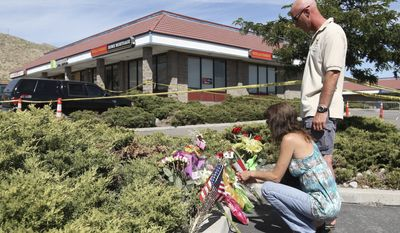 Donna Eldred and Don Bourcier lay flowers at a small memorial at the IHOP in Carson City, Nev., on Wednesday, the day after Eduardo Sencion (left) fatally shot four and wounded seven before killing himself. (Associated Press)