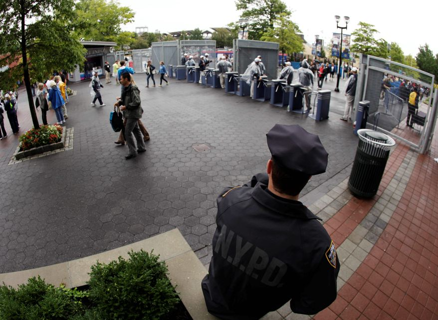 ASSOCIATED PRESS An officer stands watch at an entrance to the U.S. Open  in New York. Extra precautions are being taken at sports events Sunday, the 10th anniversary of the 9/11 attacks.