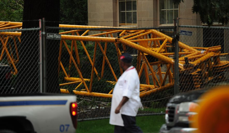 A crane collapses at Washington National Cathedral causing one injury and damage to a nearby building and crushing parked cars in Washington, DC, Wednesday September 7, 2011. (Andrew Harnik / The Washington Times)