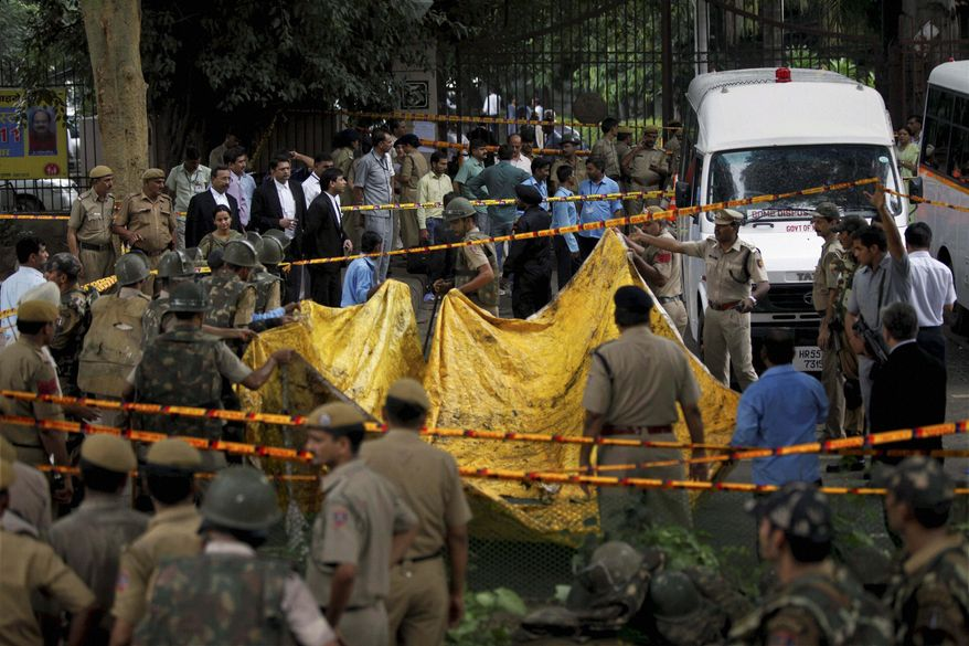 Indian police officers prepare to cover the scene of a blast outside the High Court in New Delhi on Wednesday, Sept. 7, 2011, after a bomb apparently hidden in a briefcase exploded in the deadliest attack in the Indian capital in nearly three years. (AP Photo)
