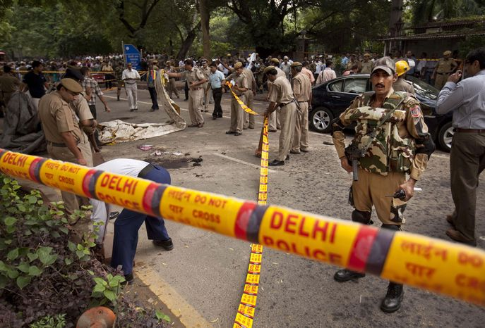 Indian police secure the scene of a blast outside the High Court in New Delhi on Sept. 7, 2011. A bomb apparently hidden in a briefcase exploded outside a gate crowded with petitioners waiting to enter the building. (Associated Press)