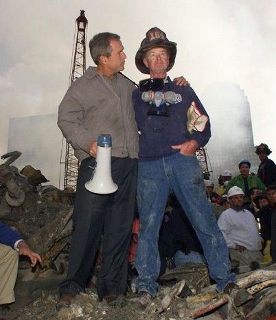 ** FILE **  President Bush embraces New York City firefighter Bob Beckwith while standing in front of the collapsed World Trade Center buildings in New York on Sept. 14, 2001. Mr. Bush famously used a bullhorn to reassure ground zero rescue workers, the American public and the world that the terrorists would soon be hearing from the U.S. (Associated Press)