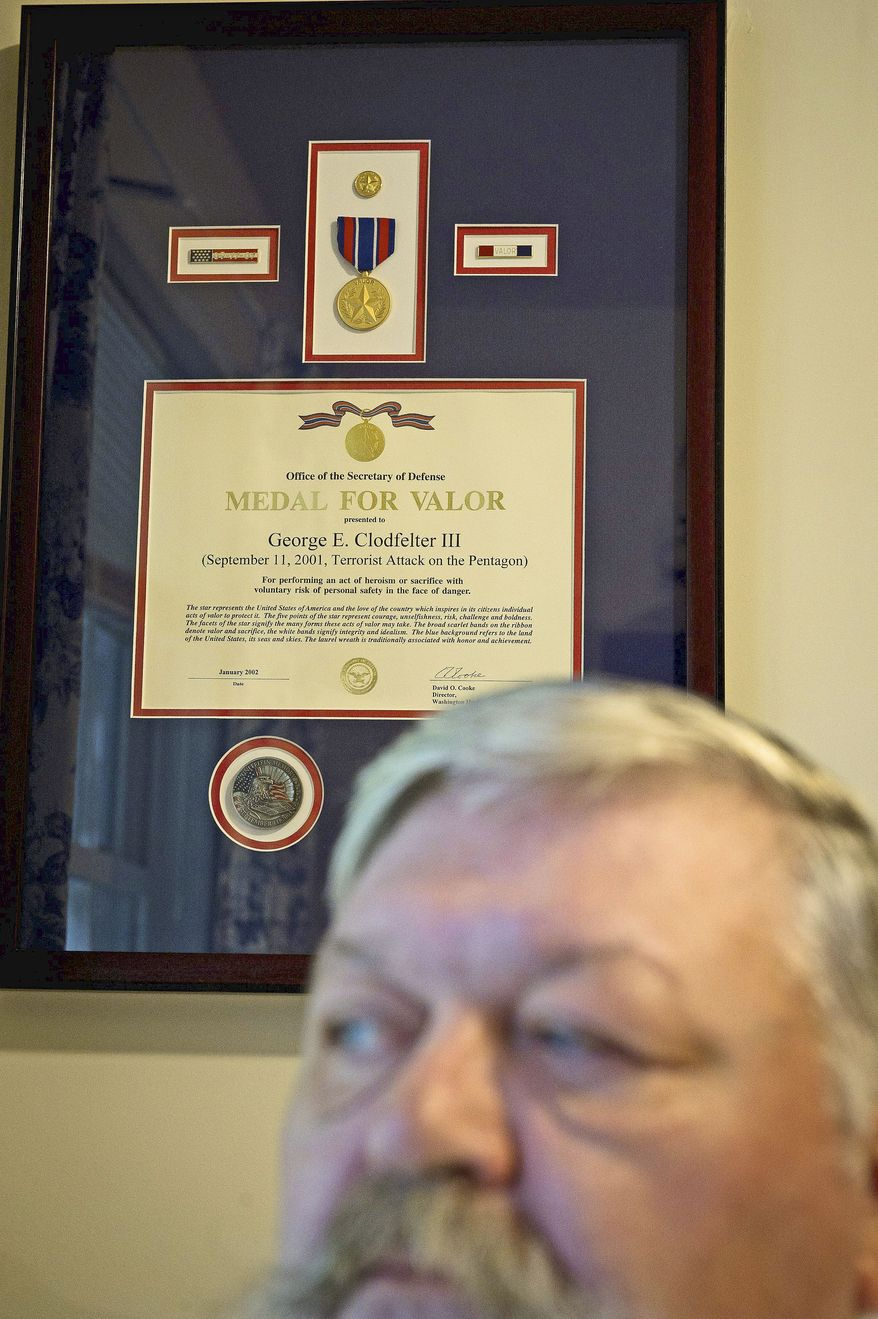 The Medal for Valor presented to George E. Clodfelter III for his actions at the Pentagon on Sept. 11, 2001, is displayed on the wall behind him in his home. He continually went into the building to rescue survivors. (Rod Lamkey Jr./The Washington Times)