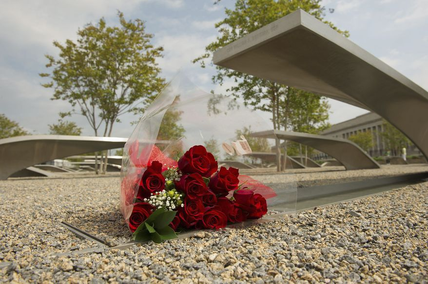 Red roses sit beneath the bench honoring Navy Cmdr. William H. Donovan at the National 9/11 Pentagon Memorial in Arlington. The memorial is dedicated to the 184 people who were killed when a hijacked plane was flown into the Pentagon on Sept. 11, 2001. (Barbara L. Salisbury/The Washington Times)