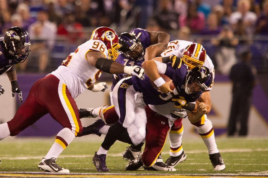 Ryan Kerrigan, Barry Cofield, and Trent Williams of the Washington Redskins take down quarterback Joe Flacco of the Baltimore Ravens in preseason football at M&T Bank Stadium in Baltimore, MD, Thursday, August 25, 2011. (Andrew Harnik / The Washington Times)  91 96 72