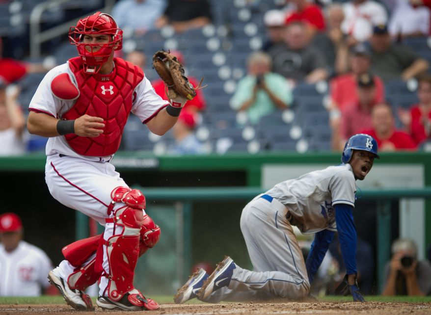 Rod Lamkey Jr./The Washington Times The Ddogers' Dee Gordon reacts after being tagged out at the plate by Wilson Ramos on Thursday during the third inning at Nationals Park. Severe weather continued to mess with the Nationals' schedule as Game 2 was rained out.