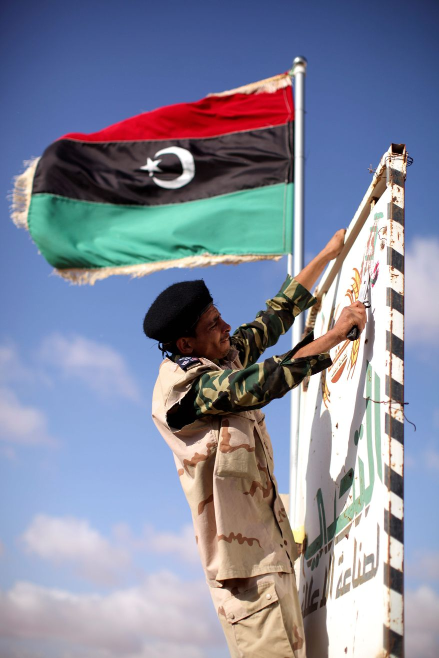 Associated Press photographs Above: Libyan rebels head to the front line Thursday through the last checkpoint before Bani Walid, Libya. Thousands of rebels have converged on Bani Walid and have threatened to attack if residents don't surrender by Saturday. A number of regime loyalists are thought to be there. Top: A rebel removes Gadhafi slogans from a roadside sign.