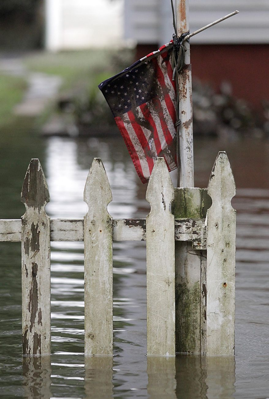 A U.S. flag hangs near a picket fence as floodwaters cover the front yard of a home, Thursday, Sept. 8, 2011, in Lincoln Park, N.J. Residents along the Passaic River are still cleaning up after Irene with the remnants of Lee expected to drop anywhere from two to five inches of rain. Forecasters say New Jersey's streams and rivers remain at or in flood stage. (AP Photo/Julio Cortez)