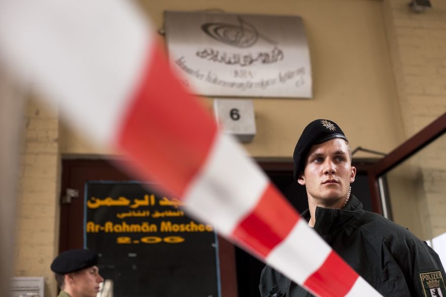 """German police officers stand guard outside an Islamic cultural center as others conduct a search inside on Thursday, Sept. 8, 2011, in Berlin. Police detained two men suspected of obtaining potential ingredients for a bomb and searched the Islamic center, where the pair spent time. The sign on the building reads """"Ar-Rahman Mosque and Islamic Cultural Center for Religious Enlightenment."""" (AP Photo/Markus Schreiber)"""