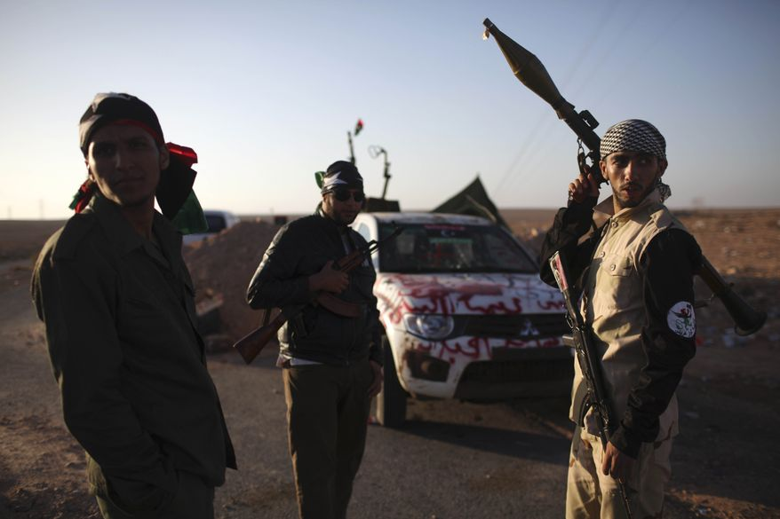 Former rebel fighters chat at the checkpoint between Tarhouna and Bani Walid on Sept. 8, 2011. Libya's former rebels have surrounded the ousted dictator Moammar Gadhafi, and it is only a matter of time until he is captured or killed, a spokesman for Tripoli's new military council said Wednesday. (Associated Press)